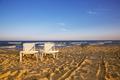 Two deckchairs on the sandy beach