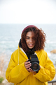 Cheerful african curly young woman wearing yellow coat holding camera.