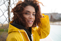 Concentrated african curly young lady wearing yellow coat
