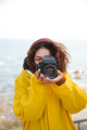 Happy african curly young woman photographer wearing yellow coat