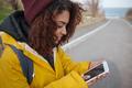 Woman near road using smartphone