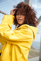 Happy african curly young lady wearing yellow coat