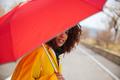 Woman hiding behind umbrella
