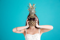 Portrait of a young girl hiding her head behind pineapple