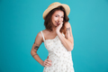 Porrtrait of a smiling playful shy woman wearing summer clothes