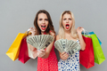 Two shocked women holding shopping bags and showing money