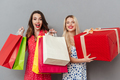 Cheerful ladies friends with bright makeup lips holding shopping bags