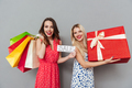 Happy young two ladies friends with shopping bags and gift