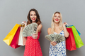 Two women holding shopping bags and showing money