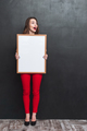 Full length portrait of surprised woman holdink blank board