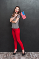 Full length portrait of smiling woman holding USA flag