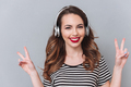 Happy young lady listening music with headphones