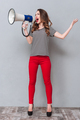 Full length portrait of woman screaming at megaphone