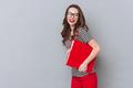 Happy woman in eyeglasses holding office folder