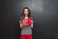 Smiling woman opening a gift box