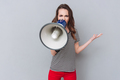 Screaming young pretty lady holding loudspeaker