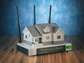 Home wireless network. House and wi-fi router on wooden table an