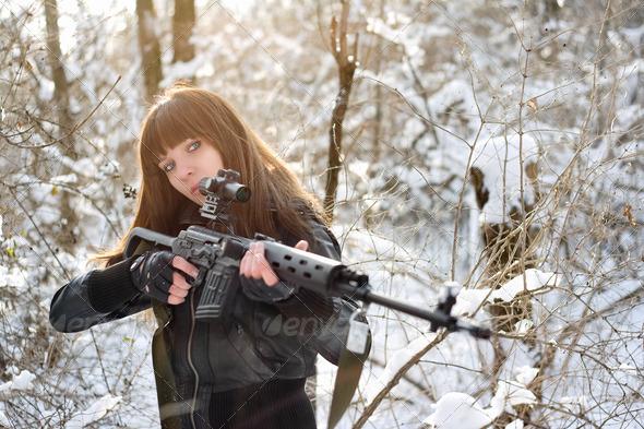 Brunette girl aiming a gun - Stock Photo - Images