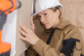 construction female worker ligning house wall