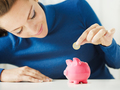 Young Woman Saving One Euro Coin In Piggy Bank