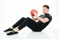 Portrait of a young healthy athlete man doing abdominal exercises