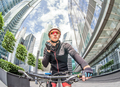 young man cyclist rides on bicycle at street among skyscrapers
