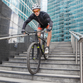 sportsman cyclist on bicycle down the stairs on urban background