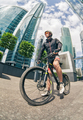 young man cyclist stand with bicycle at street among skyscrapers