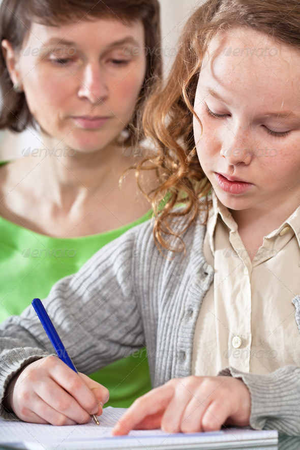 Girl doing prework with her mom - Stock Photo - Images