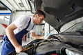 Man Working In Car Repair Shop As Mechanic Reviewing Engine Oil