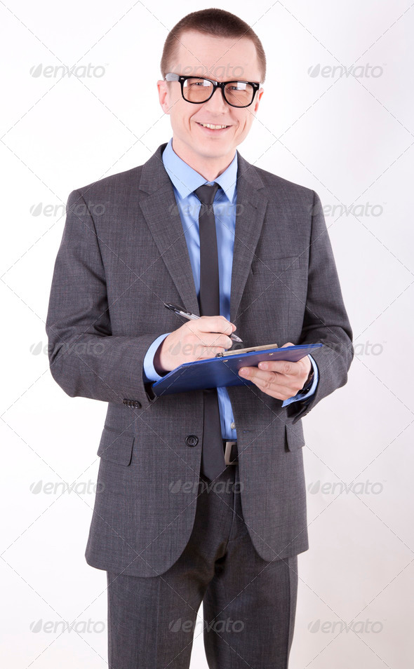 Young business man standing and smiling - Stock Photo - Images