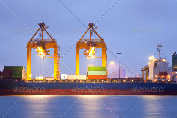 Cargo ship in port at dusk - Stock Photo - Images
