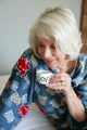 Grey-haired lady drinking her morning coffee
