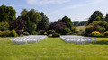 Rows of wooden chairs set up for wedding