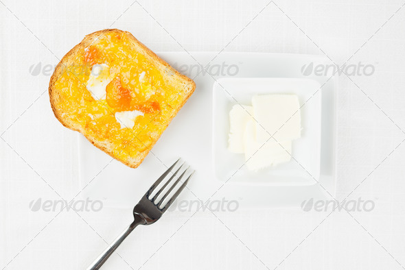 French toast, orange marmalade, butter, fork on white tablecloth - Stock Photo - Images