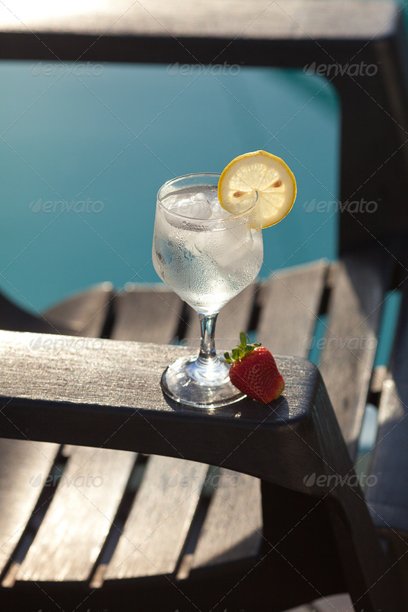 Swimming pool, lounge, a wine glass with ice, lemon and strawberry - Stock Photo - Images