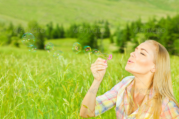 Cute girl blowing bubbles outdoors - Stock Photo - Images