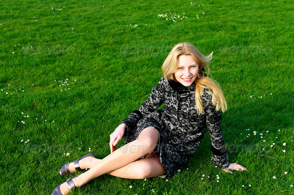 Happy girl sits on a blooming spring meadow in the early morning - Stock Photo - Images