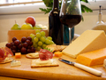 Selection of cheese and crackers with grapes and wine in the background - PhotoDune Item for Sale
