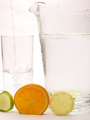 Slice of Lemon, Lime and Orange with a jug of water and a glass with water being poured in - PhotoDune Item for Sale