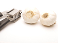Garlic press and two cloves of garlic - PhotoDune Item for Sale