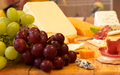 Selection of cheese and crackers with grapes in the foreground - PhotoDune Item for Sale