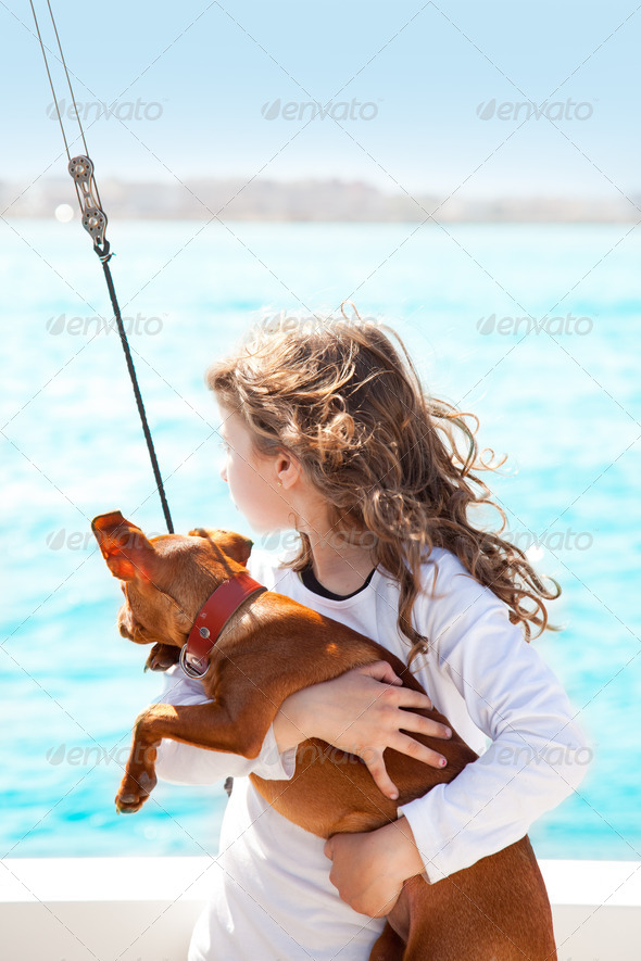 brunette kid girl with dog on the sea - Stock Photo - Images