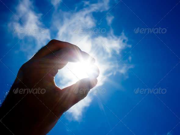 Hand holding coin against sun - Stock Photo - Images