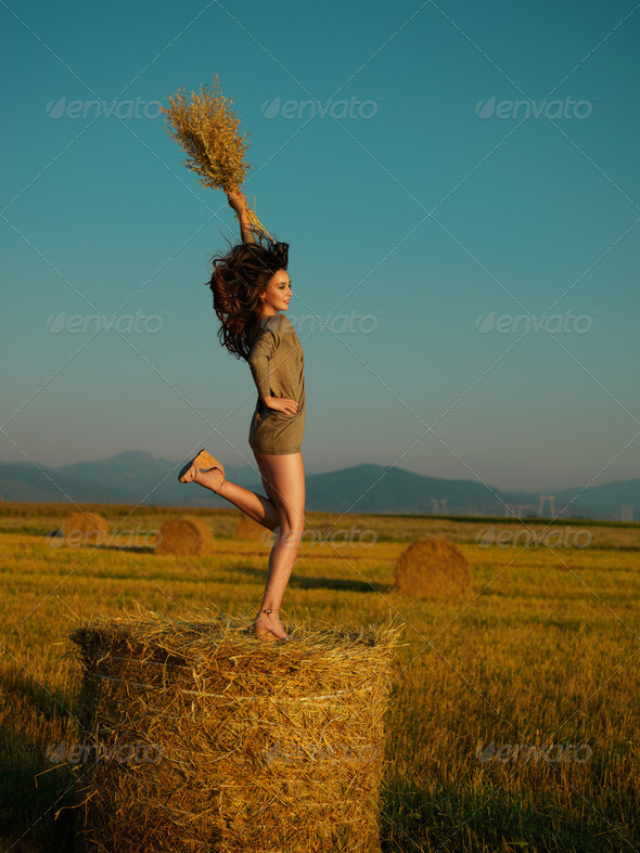 happy, young woman jumping on hay stack - Stock Photo - Images