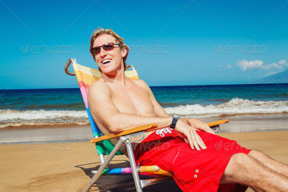 Young Man Relaxing at the Beach - Stock Photo - Images