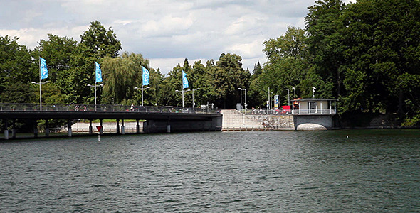 Bridge At Lake With Waving Flags Cars And People
