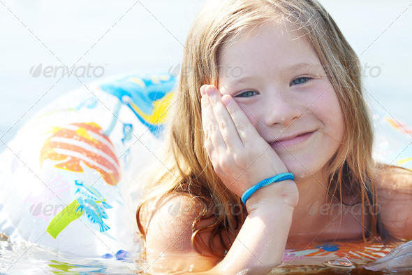 portrait of a beautiful little girl with a color lifebuoy - Stock Photo - Images