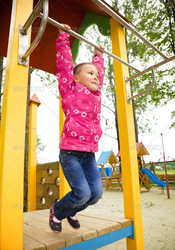 Cute little girl is playing in playground - Stock Photo - Images