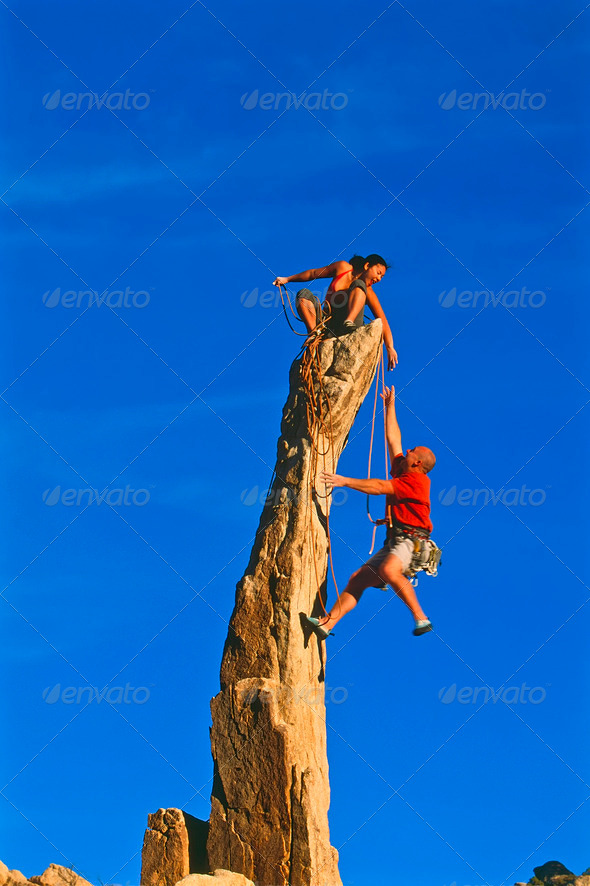 Rock climbing team reaching the summit. - Stock Photo - Images